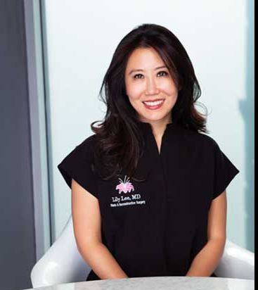 Dr. Lee smiling in her office while wearing her Lily Lee, MD Scrubs