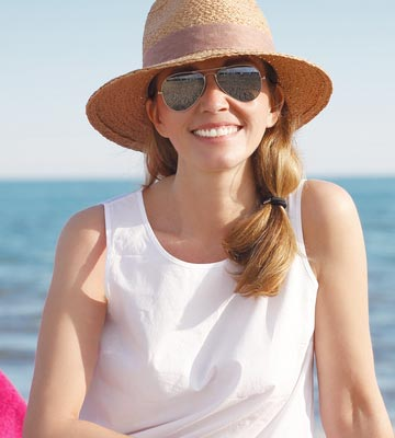 woman smiling while wearing brimmed hat on the beach